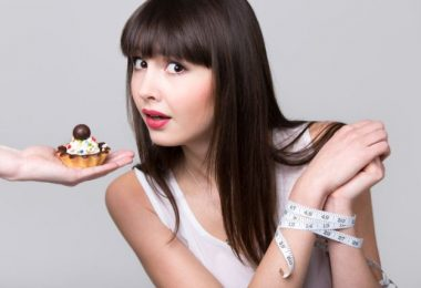Young dieting woman with hands tied with measurement tape sitting in front of tart cake, got caught while trying to reach it and take a bite, studio, gray background, isolated